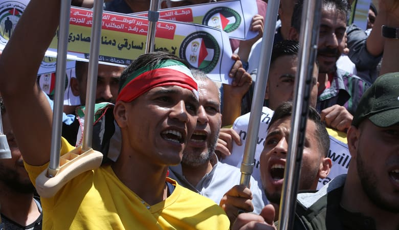 Palestinians hold placards as they take part in a protest against Israel's plans to annex parts